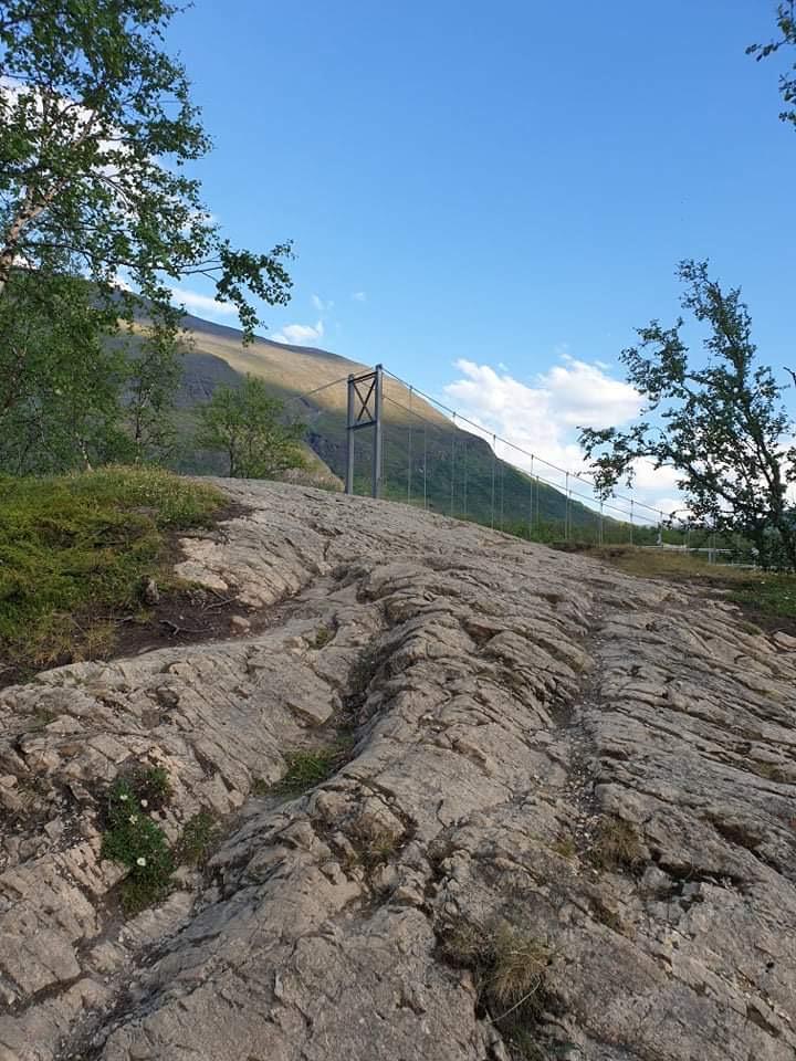 Steniga klippblock i fjällmark som leder bort där man ser en hängbro bakom krönet. I bakgrunden ett brunt berg under blå himmel.