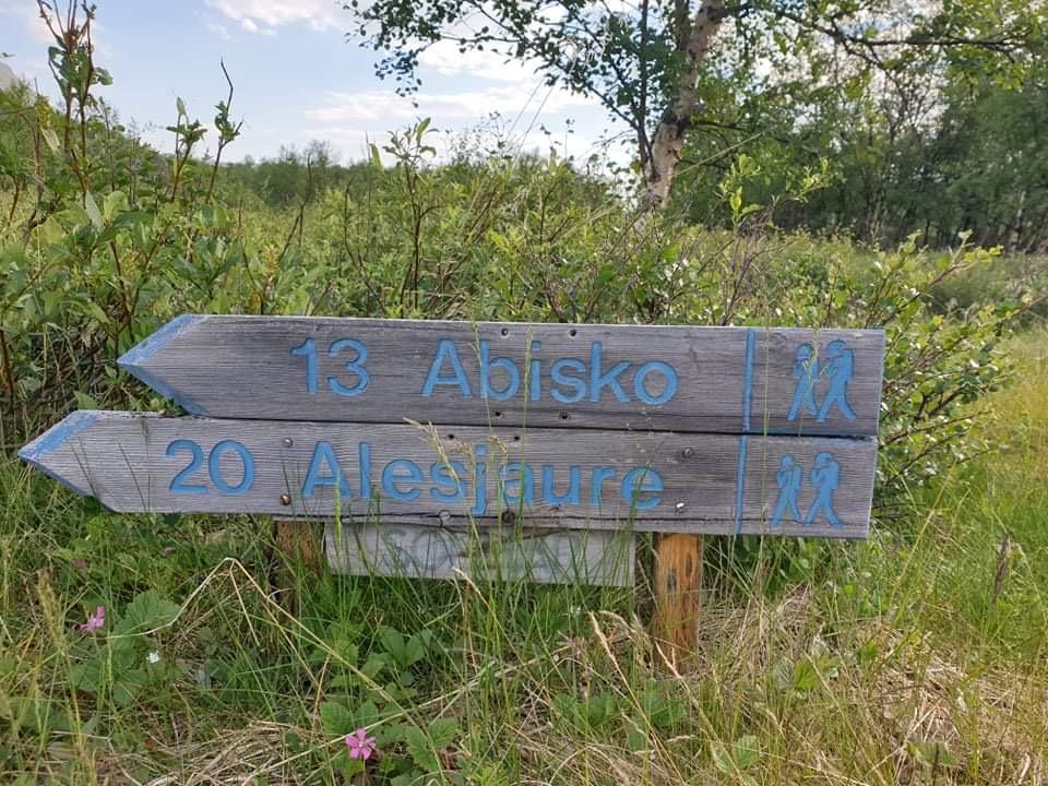 """Grå träskylt med texten """"13 Abisko"""" och under det """"20 Alesjaure"""". I bakgrunden högt gräs och grönt träd."""