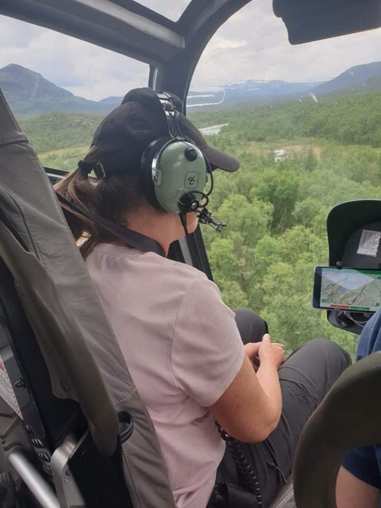 Jag sitter i helikopter med utsikt över den grönskande fjällmarken med träd, vatten och berg. Jag har på mig en lila t-shirt, mörk keps och ett grönt headset.