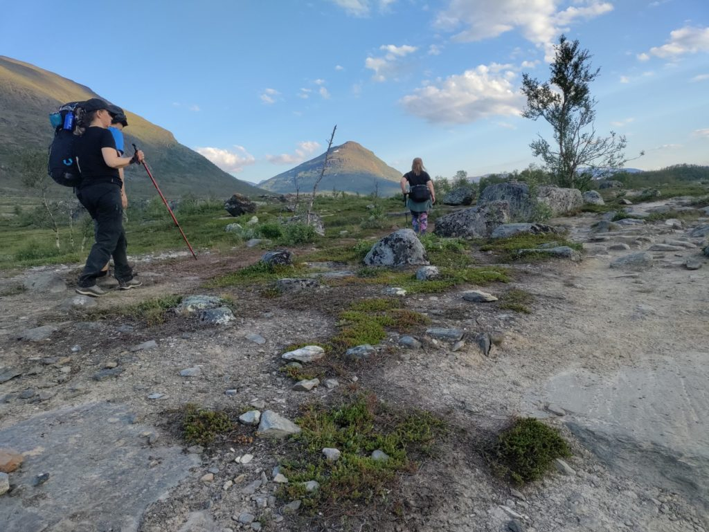 Jag och Martin går över ett öppet landskap med en kvinna en bit bort. Terrängen är stenig med kullar och berg i bakgrunden. Jag har svart klädsel, keps, ryggsäck och röda stavar. Av Martin syns mörk hatt och blå tröja.
